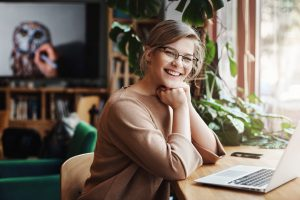 charming-carefree-european-female-with-fair-hair-glasses-sitting-near-window-laptop-leaning-hands