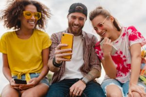 happy-young-company-smiling-friends-sitting-park-using-smartphones