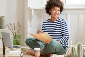 positive-black-woman-sits-crossed-legs-dressed-striped-sailor-sweater-holds-some-papers-busy-with-preparing-report